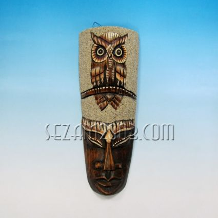 Wooden wall mask decorated with sand